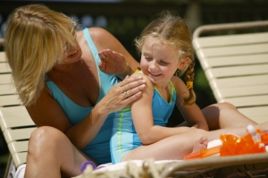 Mother applying sunscreen to her daughter